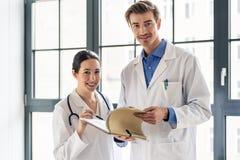 Dwa dedykującej lekarki ono uśmiecha się podczas gdy trzymający falcówkę z książeczkami zdrowia zdjęcia stock