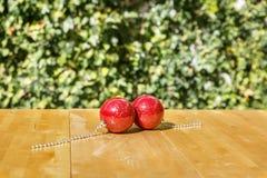 Dwa dekoracyjnej czerwonej Bożenarodzeniowej piłki wpólnie na stole Obraz Stock