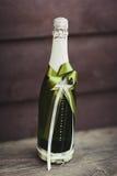 Dwa dekorującej butelki szampan i brandy jako państwo młodzi na ślubnym obiadowym stole obraz royalty free