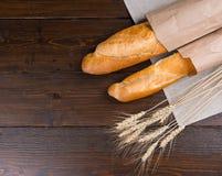Dwa delectable chlebowego bochenka i wysuszonych pszenicznych rośliny Zdjęcia Stock