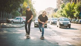 Dwa deskorolka jeźdza przejażdżki pro łyżwa przez samochodów na ulicie obraz royalty free
