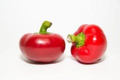 Dwa dojrzałego czerwonego pieprzu dalej nad bielem Obrazy Stock
