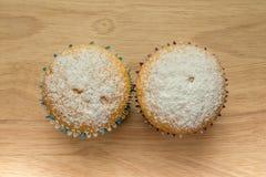 Dwa domowej roboty babeczki z sproszkowanym cukierem na drewnianej desce Zdjęcia Royalty Free