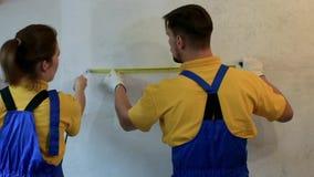 Dwa dorosłego repairmen w błękitnych coveralls robią pomiarom z ruletą Żeński pracownik robi notatkom zdjęcie wideo