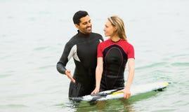Dwa dorosłych surfingowów pary talia głęboko w morzu Fotografia Royalty Free