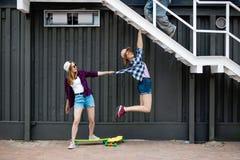 Dwa dosyć one uśmiechają się blond dziewczyny jest ubranym w kratkę koszula, nakrętki i drelichowych skróty, balansują przed czar zdjęcia stock