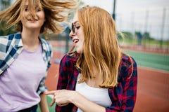 Dwa dosyć one uśmiechają się blond dziewczyny jest ubranym w kratkę koszula stoją na sportsfield i mają zabawę Sport i chłodno obraz stock