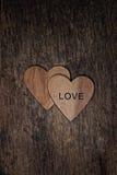 Dwa drewnianego serca z słowo miłością na drewnie textured tło Zdjęcia Stock