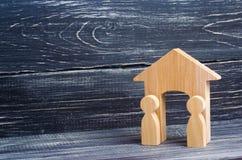 Dwa drewnianej postaci ludzie stoją blisko wejścia drewniany dom Pojęcie jest ochronny i obrończy bouncers zdjęcia stock