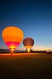 Dwa dużego balonowy przygotowywający zdejmował przy zieleni polem w mrocznym niebie Zdjęcia Royalty Free