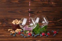 Dwa dużego szkła z owocowym sokiem Borówki, malinki, arachidy w pucharze na ciemnego brązu drewnianym tle i, mennica obraz royalty free