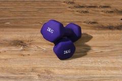 Dwa dumbbells 2 kilo na drewnianym tle Zdjęcie Royalty Free