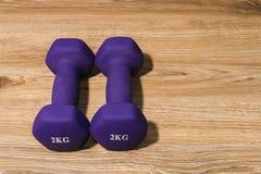 Dwa dumbbells 2 kilo na drewnianym tle Fotografia Royalty Free