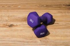Dwa dumbbells 2 kilo na drewnianym tle Fotografia Stock