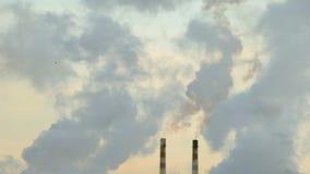Dwa dymią kominu w chmurach kontrpara zbiory