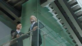 Dwa dyrektora w pozyci na drugim piętrze dyskutuje biznes zbiory