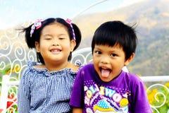 Dwa dzieci brat siedzi na ławce w lato parku Fotografia Stock