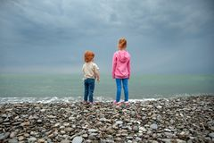 Dwa dzieci stojak na seashore i spojrzenie w odległość obraz stock
