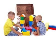 Dwa dzieci sztuka z sześcianami Duży drewniany brązu pudełko i wiele różne stubarwne zabawki dla dzieci odizolowywający dalej, zdjęcie stock