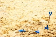 Dwa dzieciaków łopata na żółtej piasek plaży obraz stock