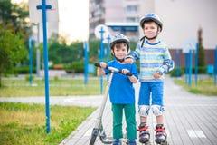 Dwa dzieciaków chłopiec na rolkowych łyżwach i jego rodzeństwo bracie na hulajnoga Zdjęcie Stock