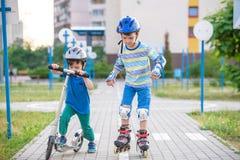 Dwa dzieciaków chłopiec na rolkowych łyżwach i jego rodzeństwo bracie na hulajnoga Zdjęcie Royalty Free