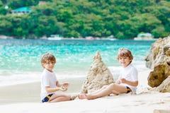 Dwa dzieciak chłopiec buduje piasek roszują na tropikalnej plaży zdjęcia stock