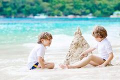 Dwa dzieciak chłopiec buduje piasek roszują na tropikalnej plaży obraz stock