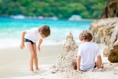 Dwa dzieciak chłopiec buduje piasek roszują na tropikalnej plaży obrazy stock