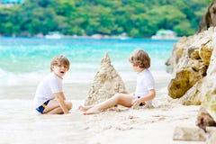 Dwa dzieciak chłopiec buduje piasek roszują na tropikalnej plaży obraz royalty free