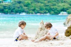 Dwa dzieciak ch?opiec buduje piasek roszuj? na tropikalnej pla?y zdjęcia royalty free