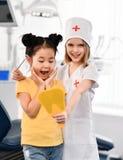 Dwa dzieciak dziewczyny bawić się dentysty i szczęśliwego pacjenta w stomatologicznym biurze zdjęcia royalty free