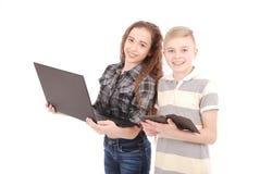 Dwa dzieciaka bawić się i target957_1_ sieć na cyfrowej pastylce i laptopie Zdjęcie Royalty Free