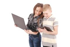 Dwa dzieciaka bawić się i target957_1_ sieć na cyfrowej pastylce i laptopie Obrazy Royalty Free