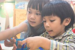 Dwa dzieciaka bawić się z edukacyjną zabawką w sala lekcyjnej obrazy royalty free