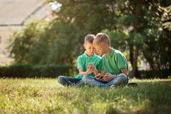 Dwa dzieciaka brata bawić się gry na smartphone z podnieceniem podczas gdy siedzący na trawie w parku fotografia royalty free