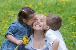 Dwa dzieciaka całuje macierzysty plenerowego Fotografia Stock