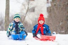 Dwa dzieciaka, chłopiec bracia, ono ślizga się z koczkiem w śniegu, wintertime Zdjęcia Stock