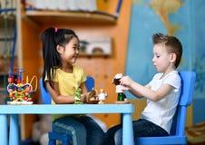 Dwa dzieciaka chłopiec i dziewczyna siedzą przy stołu i sztuki zabawki lekarkami zdjęcia stock