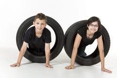 Dwa dzieciaka czołgać się przez opon obrazy stock