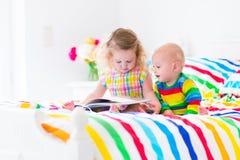 Dwa dzieciaka czyta książkę w łóżku zdjęcie royalty free