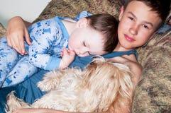 Dwa dzieciaka i pies odpoczywa w krześle obraz royalty free