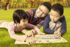 Dwa dzieciaka i tata czyta książkę podczas gdy kłamający przy parkiem Zdjęcia Royalty Free