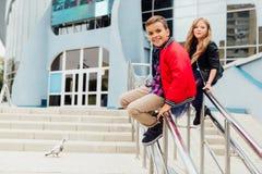 Dwa dzieciaka: Pięknych dzieci sztuka na poręczu w ulicie na schodkach Obraz Royalty Free