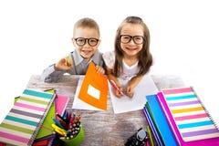 Dwa dzieciaka przy stołowymi dziećmi robi pracie domowej Obrazy Royalty Free