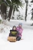 Dwa dzieciaka tobogganing obrazy stock