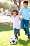 Dwa dziecka Bawić się piłkę nożną Wpólnie Obrazy Royalty Free