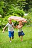 Dwa dziecka biega z parasolem w deszczu fotografia stock