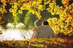 Dwa dziecka, chłopiec, siedzi na krawędzi jeziora na pogodnej jesieni zdjęcie royalty free