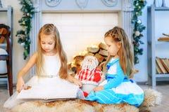 Dwa dziecka czytają książkę Pojęcie nowy rok, Wesoło boże narodzenia, hol Zdjęcie Royalty Free